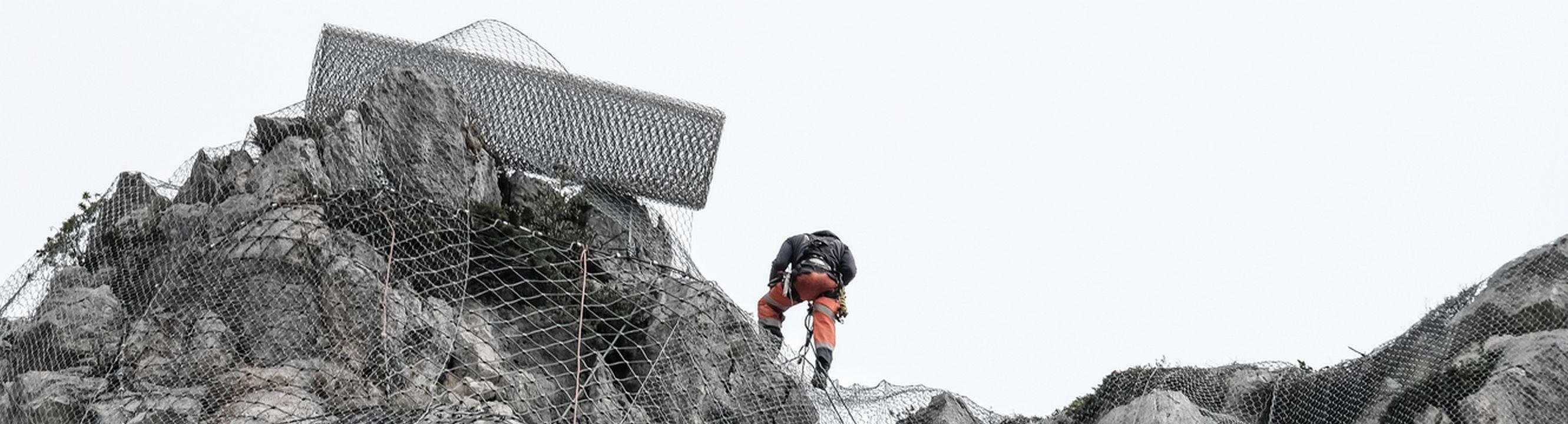 Un cordiste réalise la sécurisation d'une falaise
